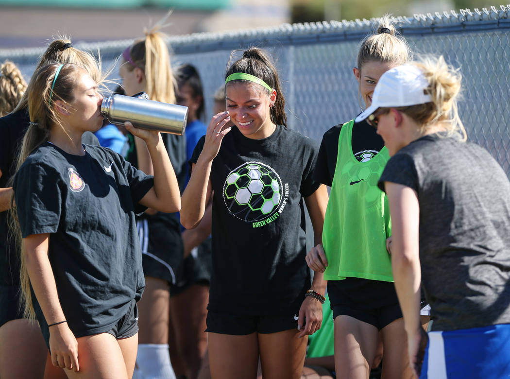 Green Valley's Taylor O'Neill, 17, laughs with her teammates as they take a water break during a team practice at Green Valley High School in Henderson, Tuesday, Sept. 18, 2018. Caroline Brehman/L ...
