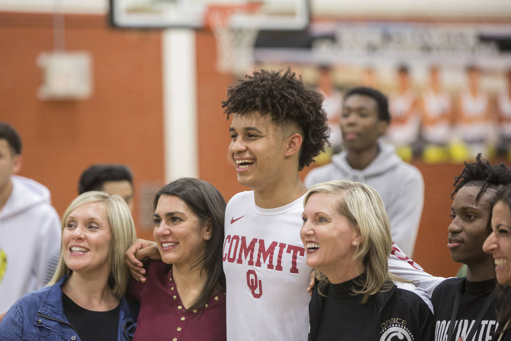 Clark senior Jalen Hill, third from left, takes photos during an event to announce his commitment to play basketball at the University of Oklahoma on Thursday, Sept. 20, 2018, at Clark High School ...