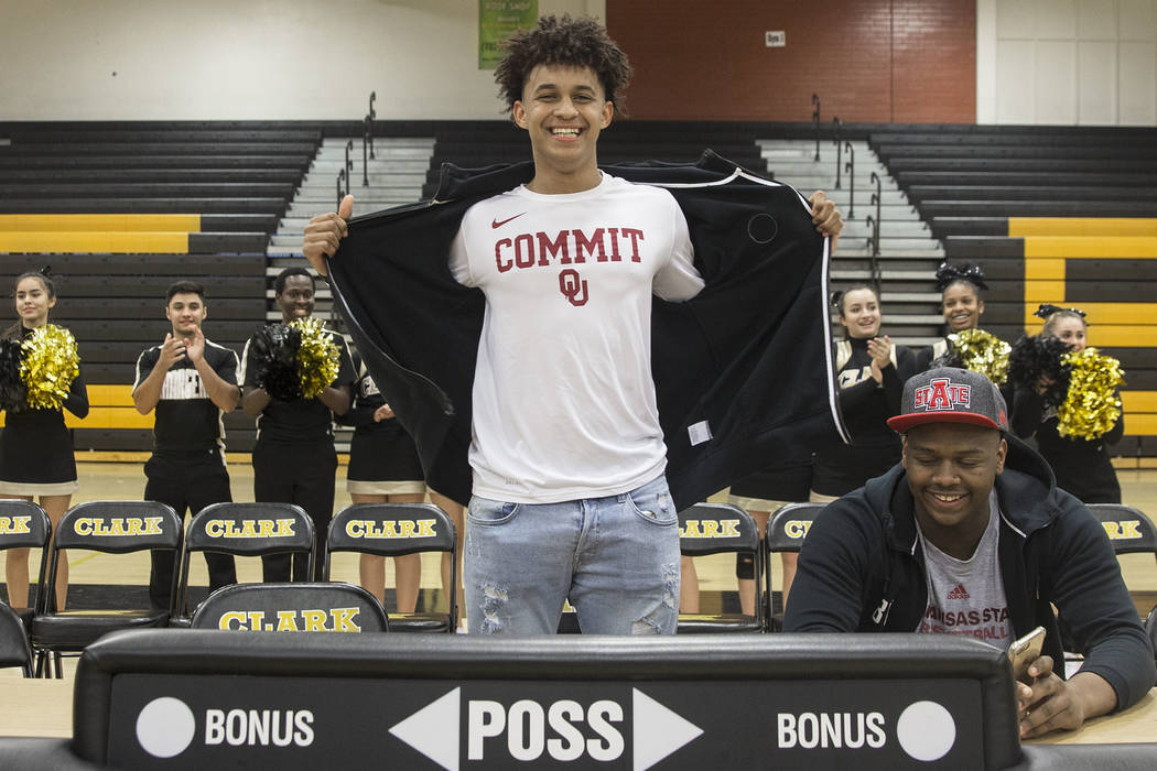 Clark senior Jalen Hill, left, shows off his Sooner colors during an event to announce his commitment to play basketball at the University of Oklahoma on Thursday, Sept. 20, 2018, at Clark High Sc ...