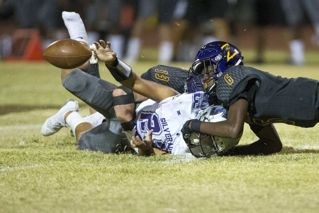 Silverado's Breven Palpallatoc (23), left, fumbles the ball as he is tackled by Durango's Michael Hayword (6) during the first half of a varsity football game at Durango High School in Las Ve ...