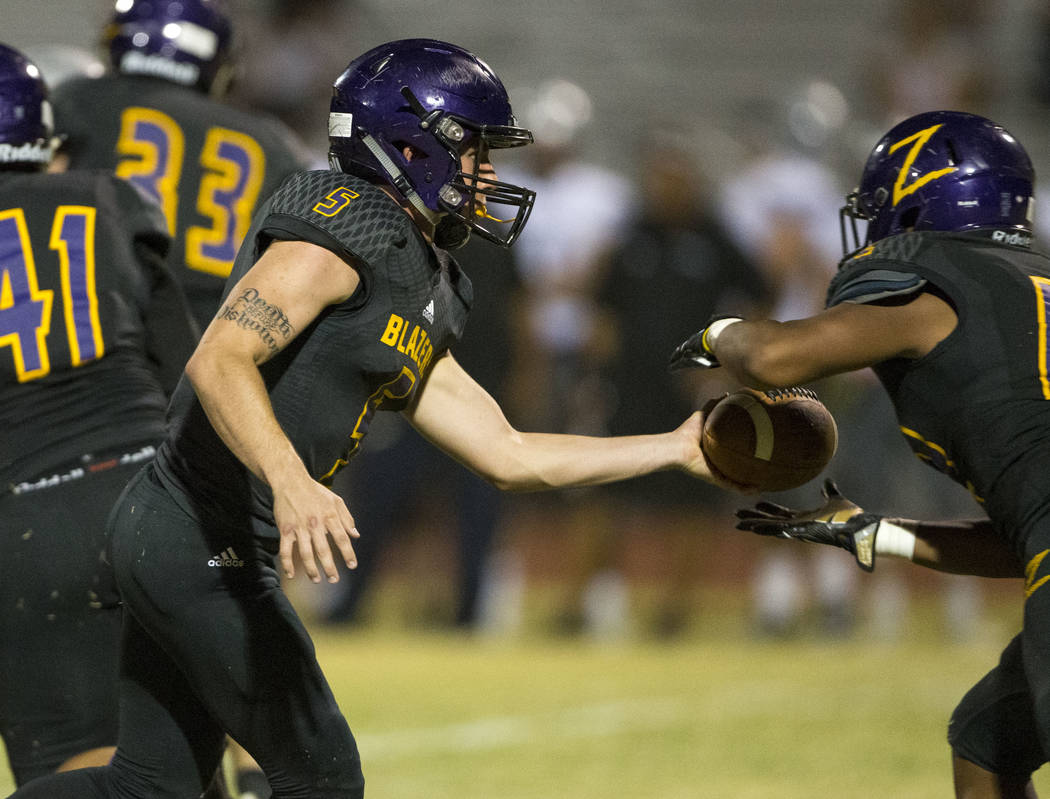 Durango's Kaden Renshaw (5), left, hands the ball off to Tau Fotu (42) during the first half of a varsity football game against Silverado at Durango High School in Las Vegas on Friday, Sept. 21, 2 ...