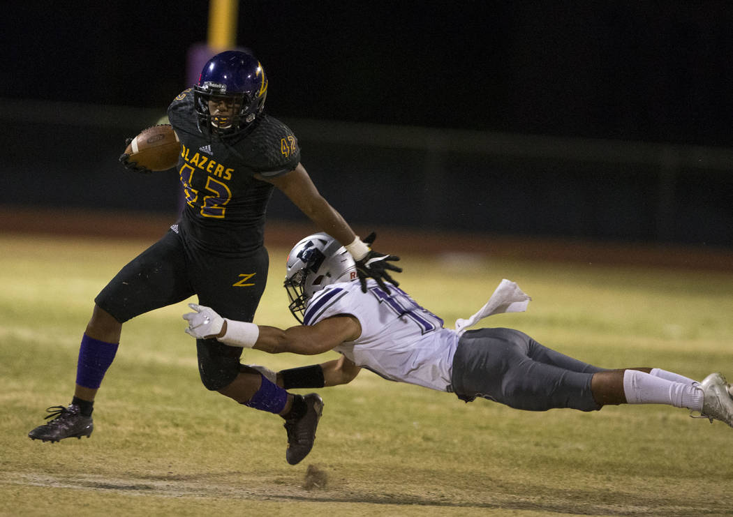 Durango's Tau Fotu (42), left, runs the ball past Silverado's Kana Hoapili (15) during the first half of a varsity football game at Durango High School in Las Vegas on Friday, Sept. 21, 2018. Rich ...