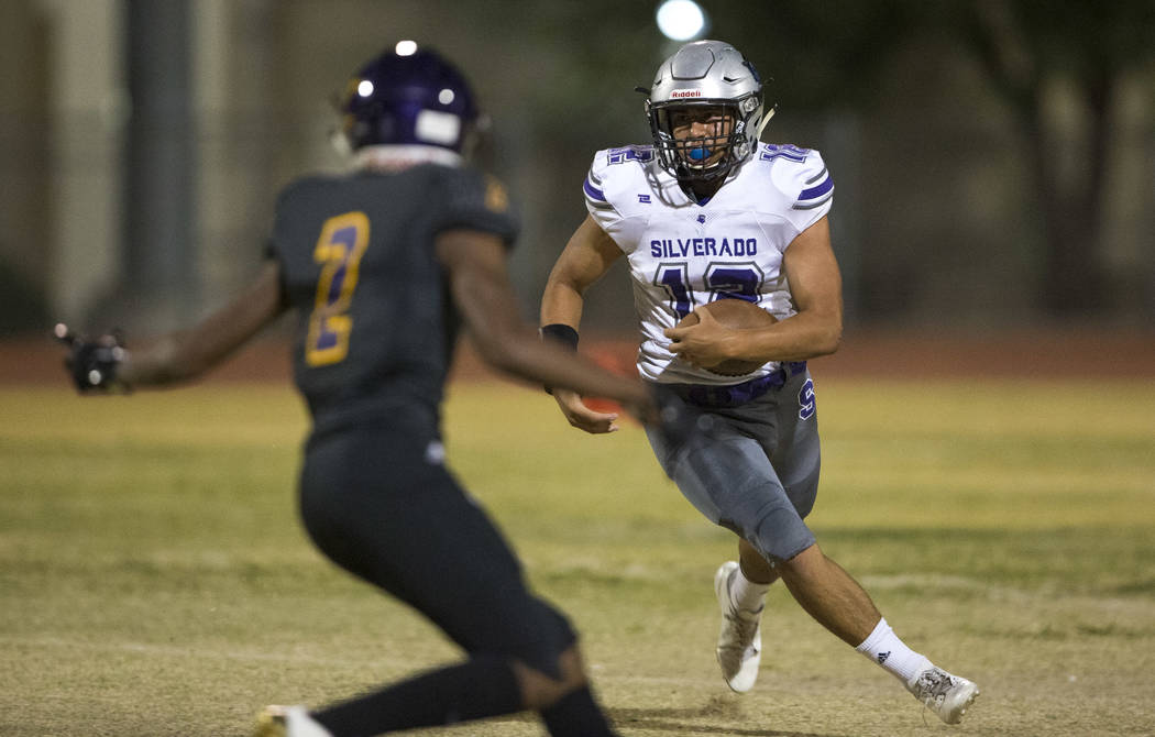 Silverado's Jacob Mendez (12), right, runs the ball as Durango's Demazje Townsend (2) closes in during the first half of a varsity football game at Durango High School in Las Vegas on Friday, Sept ...