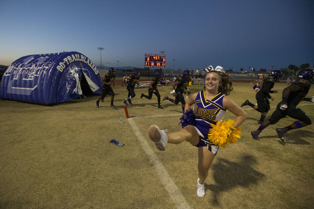 A cheerleader dances as Durango players hit the field ahead of a varsity football game against Silverado at Durango High School in Las Vegas on Friday, Sept. 21, 2018. Richard Brian Las Vegas Revi ...