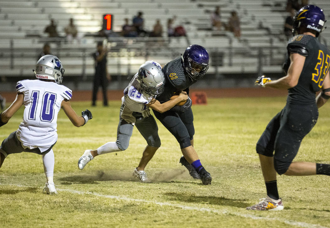Durango's Frankie Pelton (41), second right, makes his way into the end zone for a touchdown as he is tackled by Silverado's Jeremy Alipio (25) during the second half of a varsity football game at ...