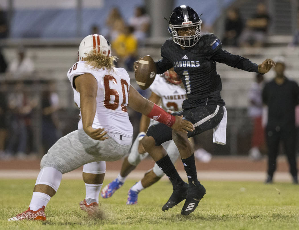 Desert Pines senior quarterback Tyler Williamson (1) makes a move past Liberty senior defensive tackle Xavier Fuamatu (60) in the first quarter during the Jaguars home game with the Patriots on Fr ...