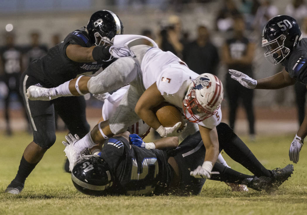 Liberty sophomore running back Ezra Tomhoon (5) leaps over Desert Pines senior defender Preston Williams (15) during the Patriots road game with the Jaguars on Friday, Sept. 21, 2018, at Desert Pi ...