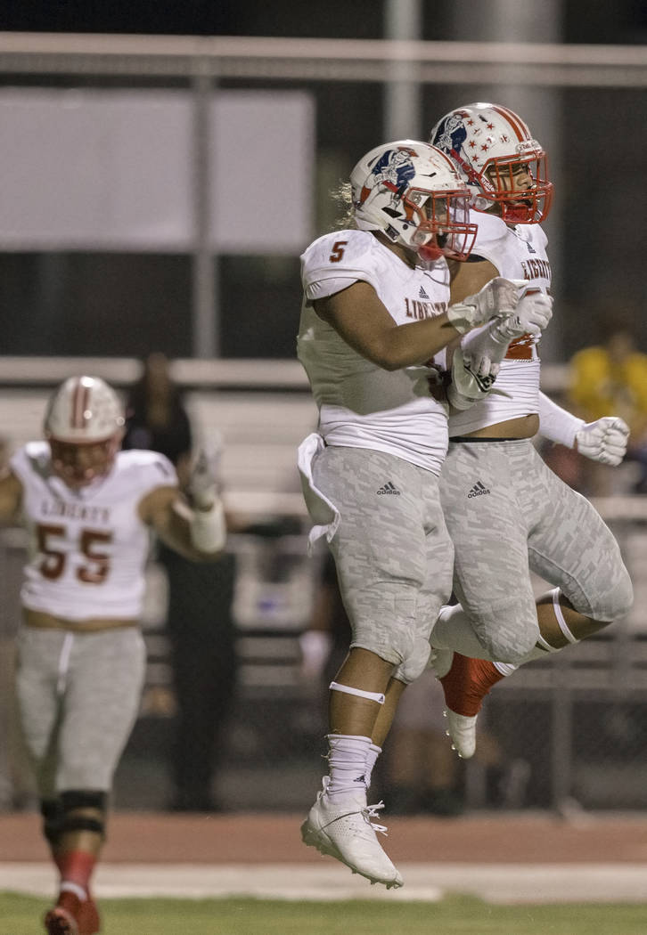 Liberty sophomore running back Ezra Tomhoon (5) celebrates with teammate Jared Tufele (27) after scoring a first quarter touchdown during the Patriots road game with the Jaguars on Friday, Sept. 2 ...