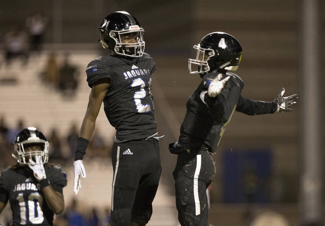 Desert Pines junior wide receiver Branden Thomas (4) celebrates after making a big catch with teammate Ezekiel Washington (21) in the second quarter during the Jaguars home game with the Patriots ...