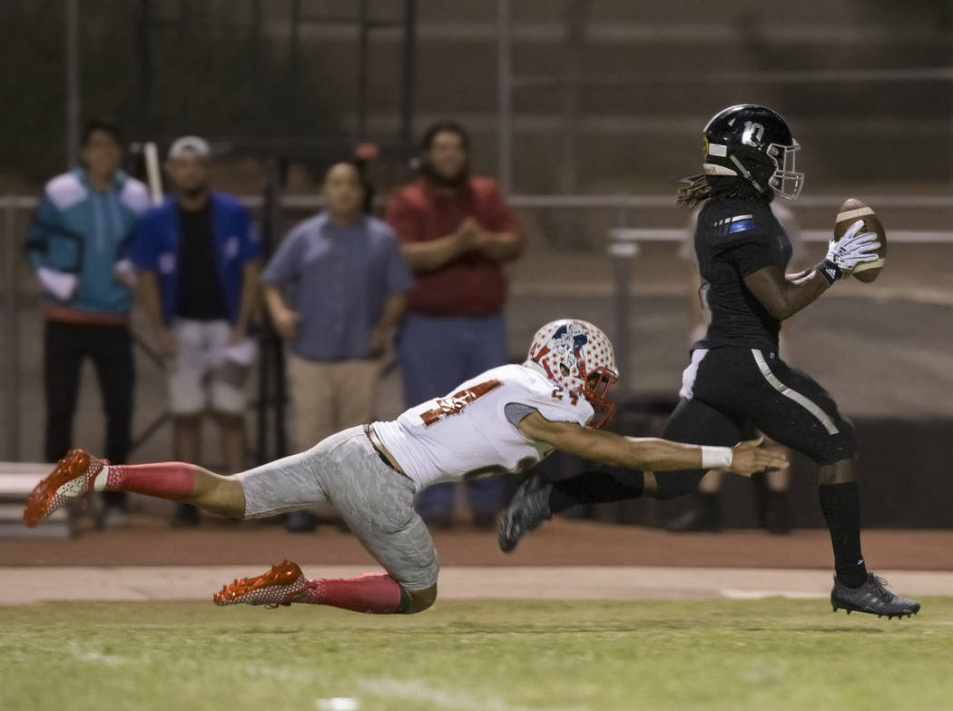 Desert Pines senior wide receiver Devin McGee (10) catches a second quarter touchdown pass against Liberty junior wide receiver Lehi Ausage (24) during the Jaguars home game with the Patriots on F ...