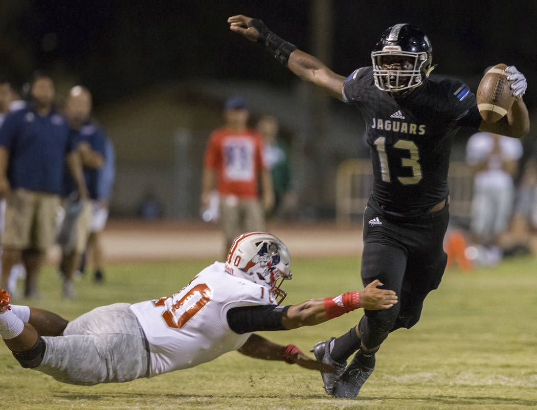 Desert Pines junior tight end Darnell Washington (13) breaks the tackle of Liberty sophomore linebacker Zephania Maea (3) in the second quarter during the Jaguars home game with the Patriots on Fr ...