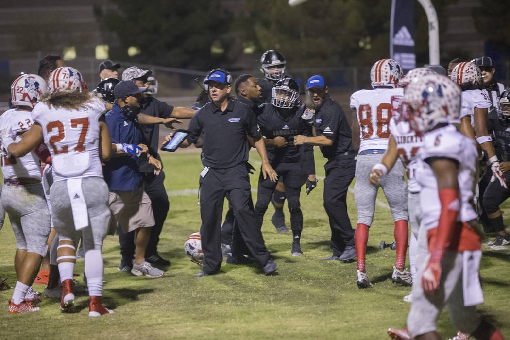 Coaches try and break up a fight in the third quarter during the Liberty Patriots road game with the Desert Pines Jaguars on Friday, Sept. 21, 2018, at Desert Pines High School, in Las Vegas. Benj ...