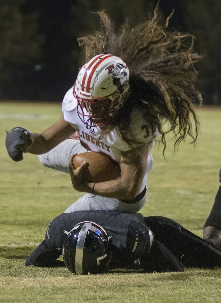 Liberty sophomore running back Zyrus Fiaseu (30) runs over Desert Pines sophomore safety Darrien Stewart (7) for a fourth quarter touchdown during the Patriots road game with the Jaguars on Friday ...