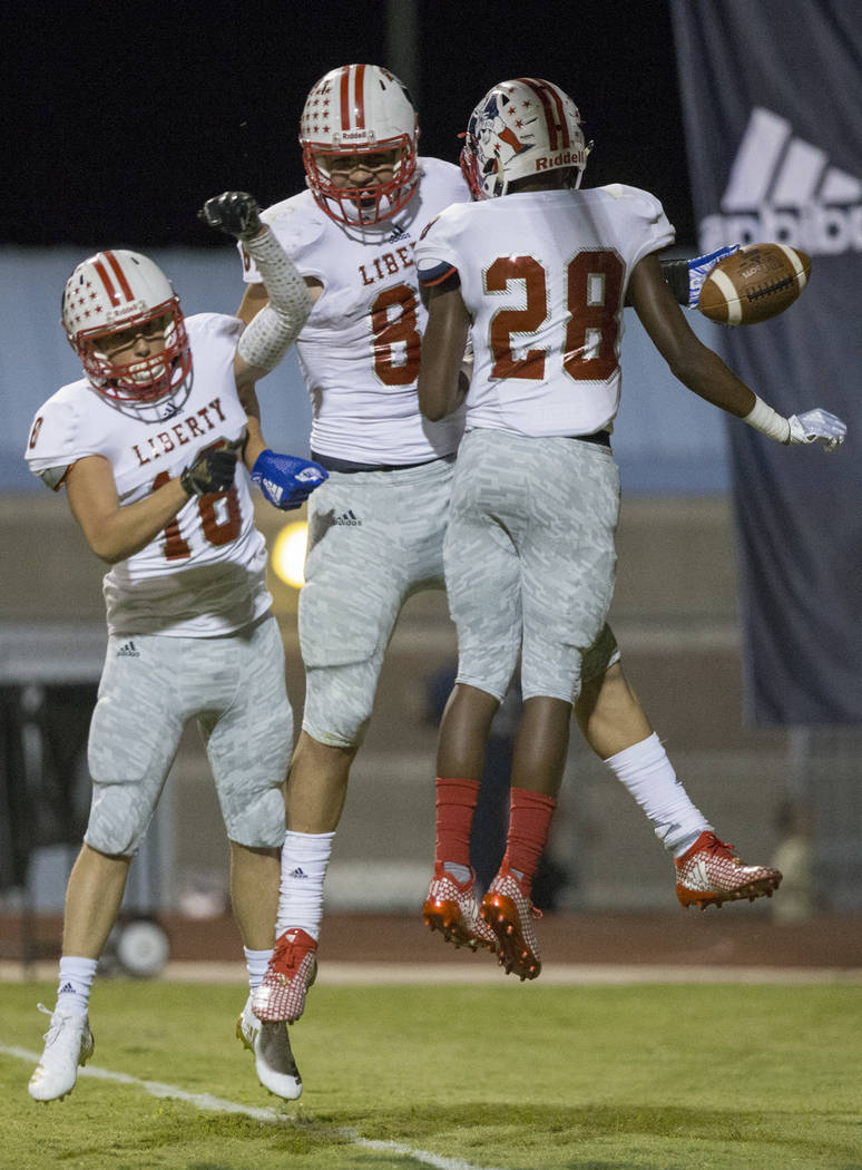 Liberty sophomore tight end Moliki Matavao (81) celebrates a fourth quarter touchdown catch with teammates Demark Colston (28) and Tyson Kohoutek (18) during the Patriots road game with the Desert ...