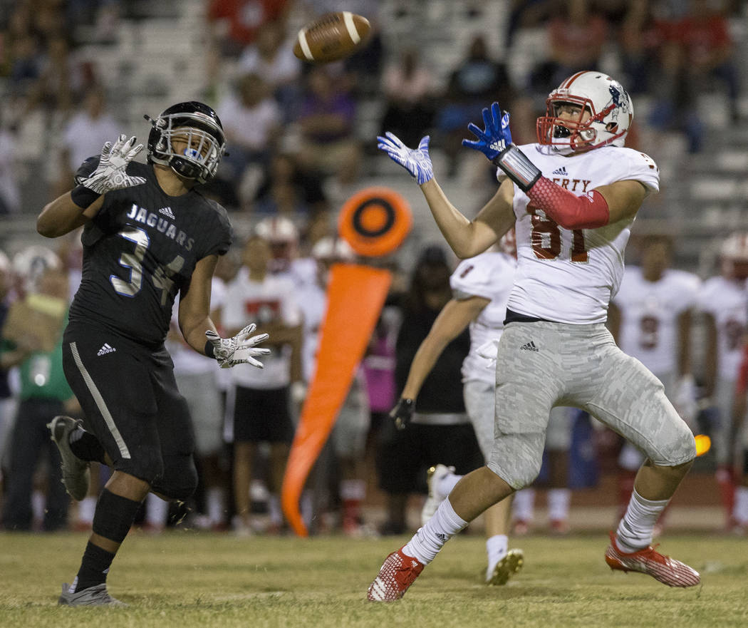Liberty sophomore tight end Moliki Matavao (81) makes a reception over Desert Pines sophomore Nikolas Salter (34) in the fourth quarter during the Patriots road game with the Jaguars on Friday, Se ...