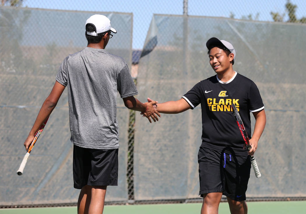 Clark's High double players Simran Shah, left, and Mark Bernales shake hands after winning their first game against Coronado High's Akhil Mohan and Colin Peltier during Desert Region boys tennis c ...