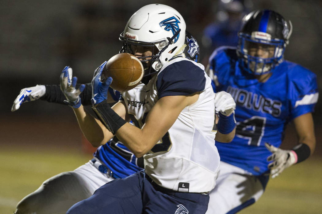 Foothill wide receiver Braeden Wilson (28) makes a catch for a touchdown past Basic defenders Brayden Maack (28), left, and Tommy Paonessa (4) during the second half of a varsity football game at ...