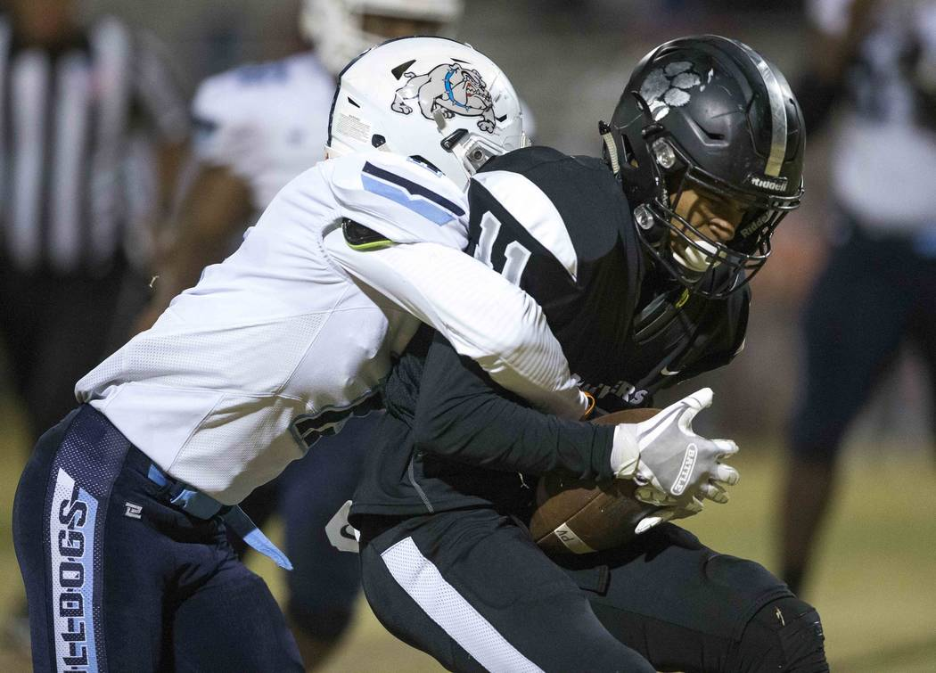 Palo Verde's Karsonne Winters (11) is tackled by Centennial's Kamden Garrett (2), left, during the second half of a varsity football game at Palo Verde High School in Las Vegas on Friday, Oct. 12, ...