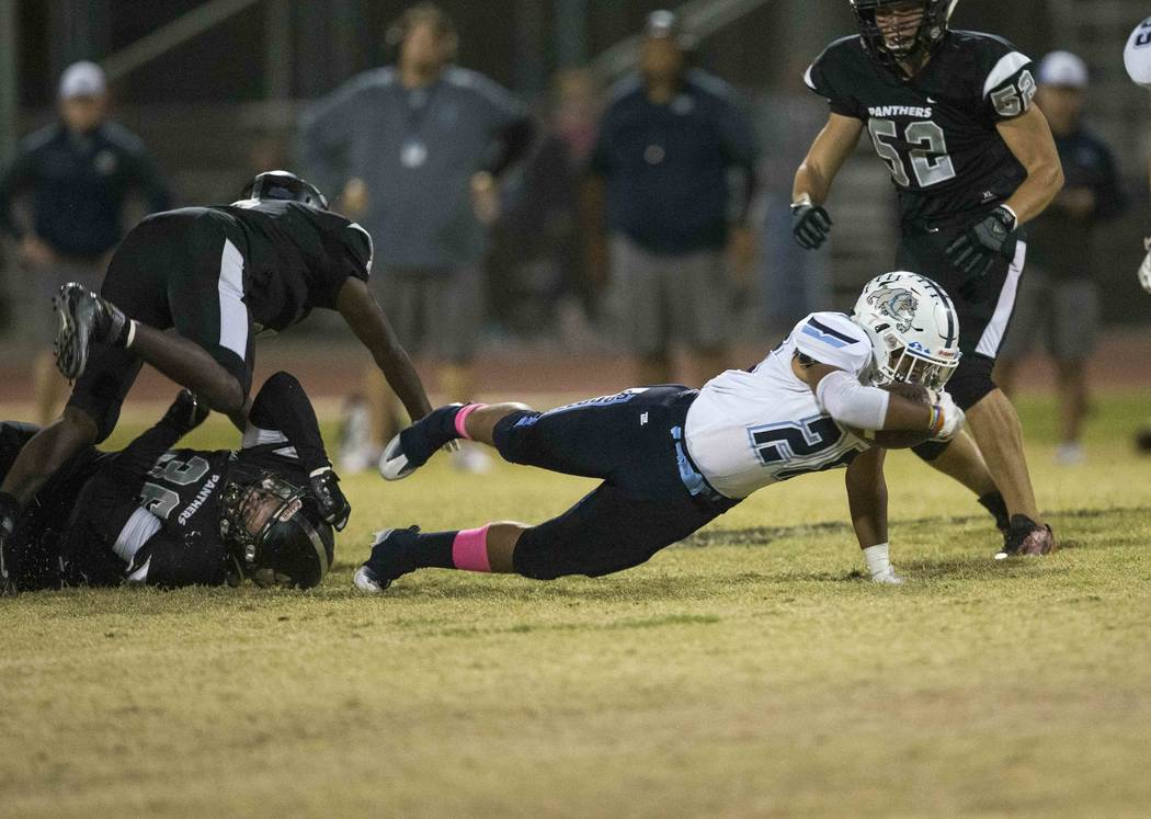 Centennial running back Marlon Thomas (28) reaches for an extra yard after breaking through Palo Verde defenders during the second half of a varsity football game at Palo Verde High School in Las ...