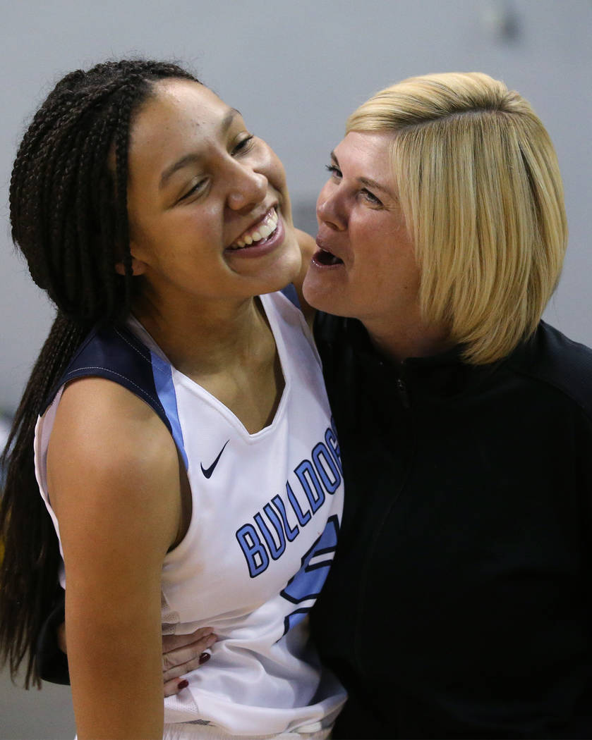 Centennial's Jade Thomas celebrates with an assistant coach after her shot at the buzzer forced the title game against Liberty into overtime at the NIAA state basketball tournament in Reno, Nev., ...