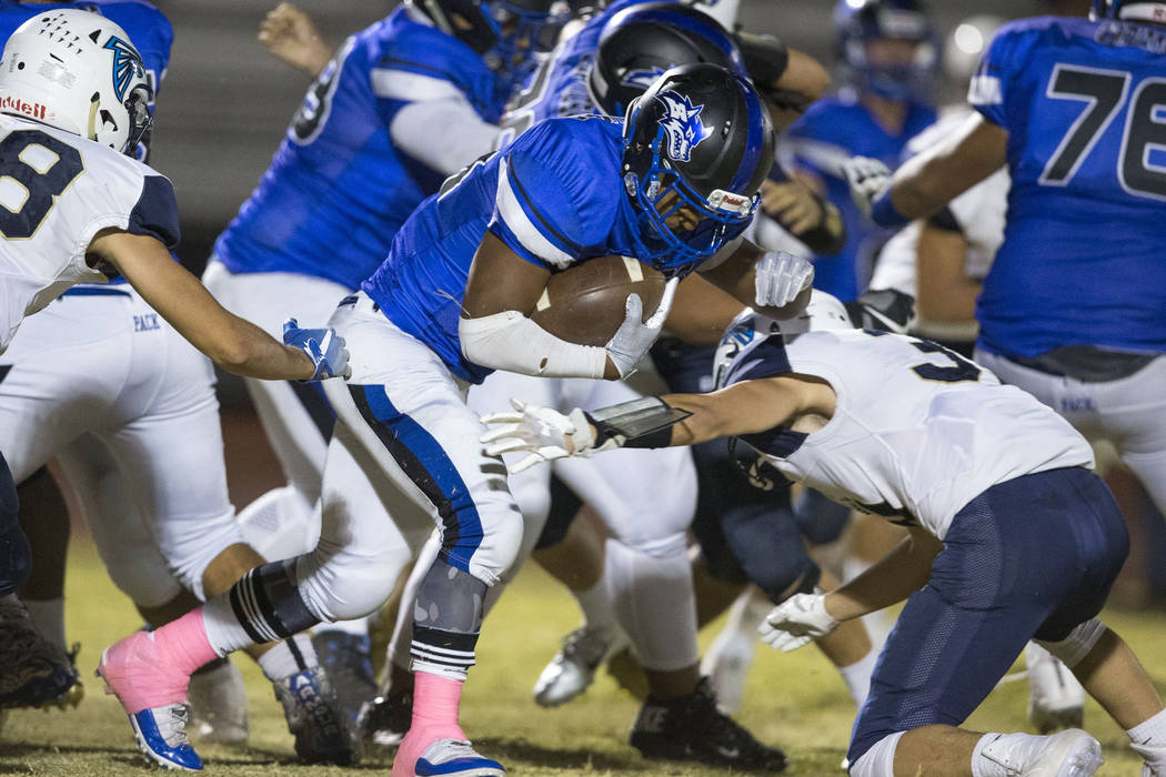 Basic running back Dorian Mcallister (21), center, carries there ball past Foothill defenders during the first half of a varsity football game at Basic High School in Henderson on Friday, Oct. 5, ...