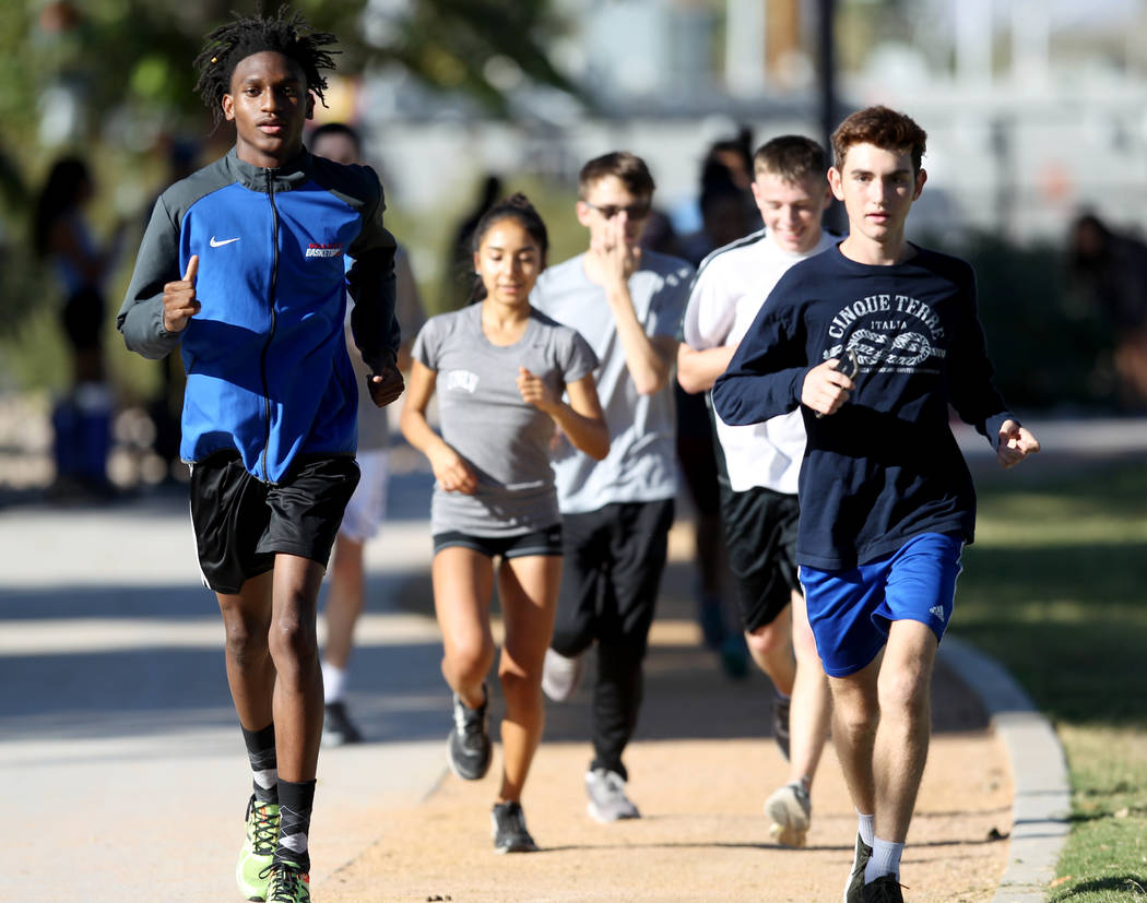 Valley High School cross country runner Christian Franklin, left, practices with teammates including Donovan Jones, right, at Justice Myron E. Leavitt Family Park in Las Vegas Wednesday, Oct. 24, ...