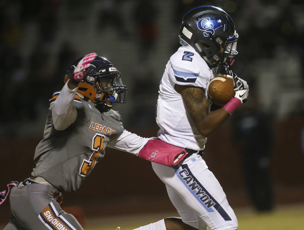Canyon Springs' Akendell Wilson (2) pulls in a reception in front of Legacy's Anthony Myles (3) during the first half of a football game at Legacy High School in North Las Vegas on Thursday, Oct. ...