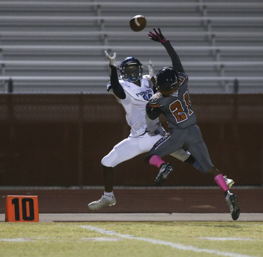 Canyon Springs' Alex Seitz (11) goes up to receive the ball as Legacy's Elijah Alvarez (21) defends during the first half of a football game at Legacy High School in North Las Vegas on Thursday, O ...