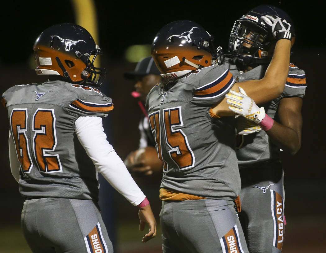 Legacy's Scott Wolkenhauer (75) celebrates a 2-point conversion scored by Legacy's Jerry Martin, right, during the first half of a football game at Legacy High School in North Las Vegas on Thursda ...