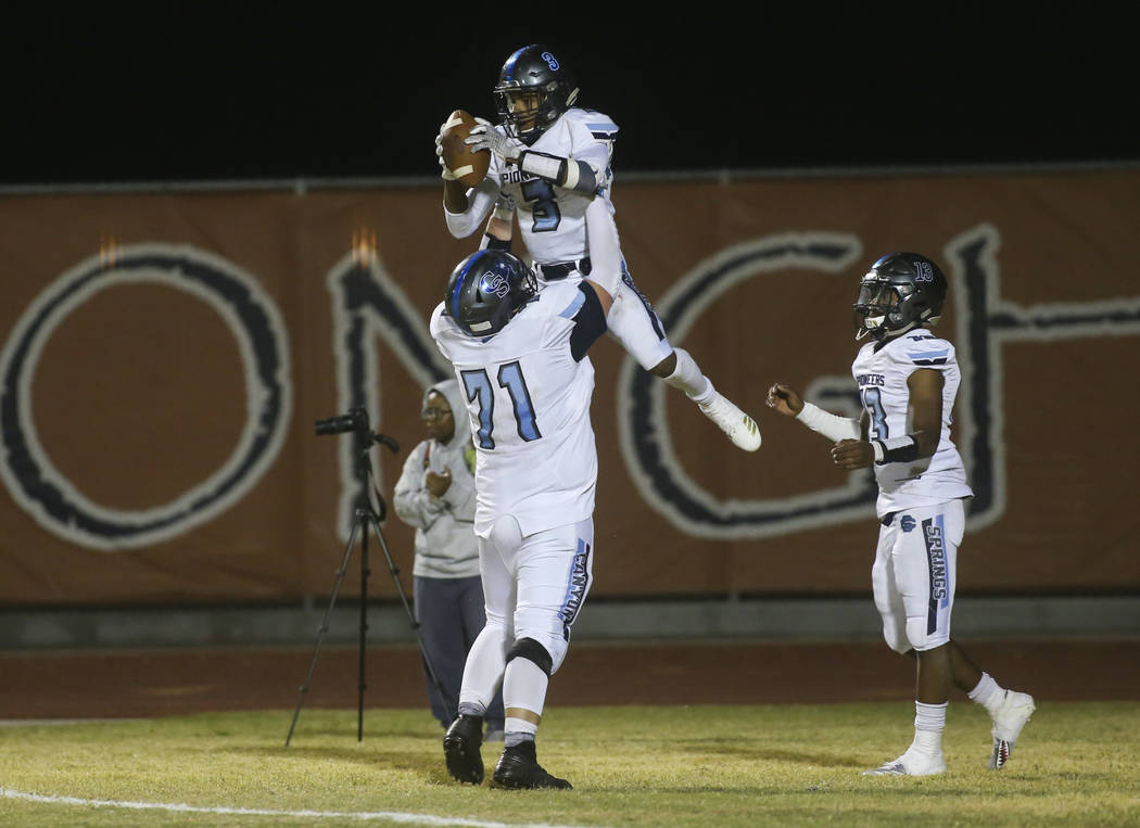 Canyon Springs' Anthony Myles (3) celebrates his touchdown with Canyon Springs' Trevor Moser (71) during the second half of a football game at Legacy High School in North Las Vegas on Thursday, Oc ...