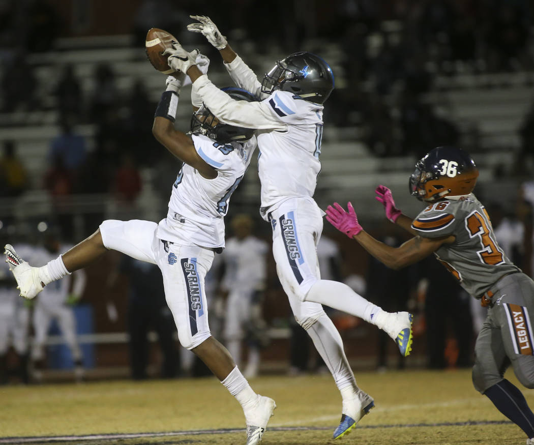 Canyon Springs' Aaron Holloway (13) and Canyon Springs' Romeo Bottley (4) block a pass intended for Legacy's Amorey Foster (36) during the second half of a football game at Legacy High School in N ...