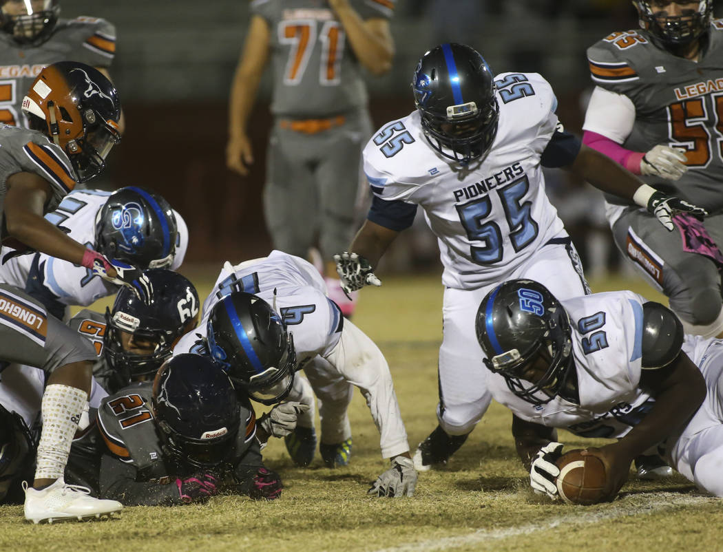 Canyon Springs' Dadraylin Tilley (50) gets possession of the ball after a fumble by Legacy's Elijah Alvarez (21) during the second half of a football game at Legacy High School in North Las Vegas ...
