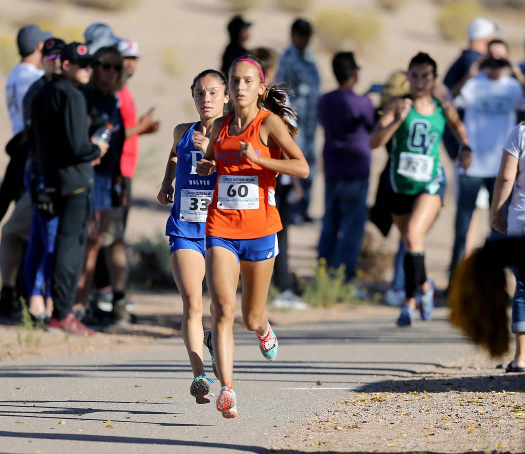 Basic High senior Raquel Chavez, left, closes in on Bishop Gorman sophomore Emilia Puskas during the 4A Desert girls region race at Veteran's Memorial Park in Boulder City Friday, Oct. 26, 2018. M ...