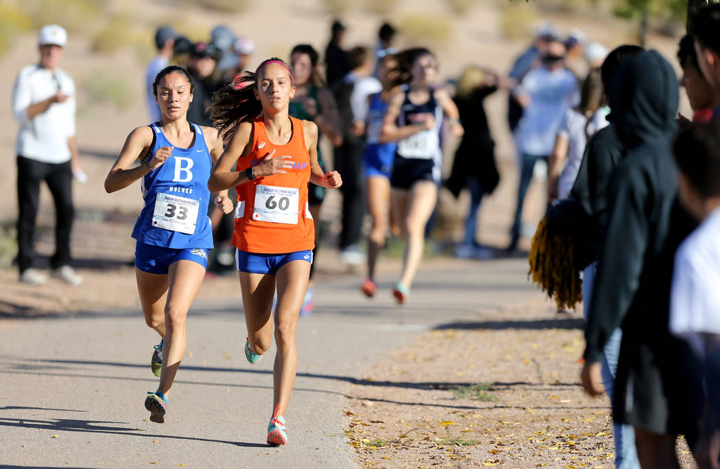Basic High senior Raquel Chavez, left, closes in on Bishop Gorman sophomore Emilia Puskas during the 4A Desert girls region race at Veteran's Memorial Park in Boulder City Friday, Oct. 26, 2018. K ...
