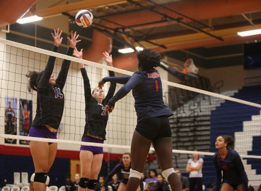Coronado's Morenike Ajayi hits the ball over the net as Durango's Tehani Faitau, left, and Lindsay McMahon attempt to block it during the Desert Region girls volleyball semifinal at Coronado High ...