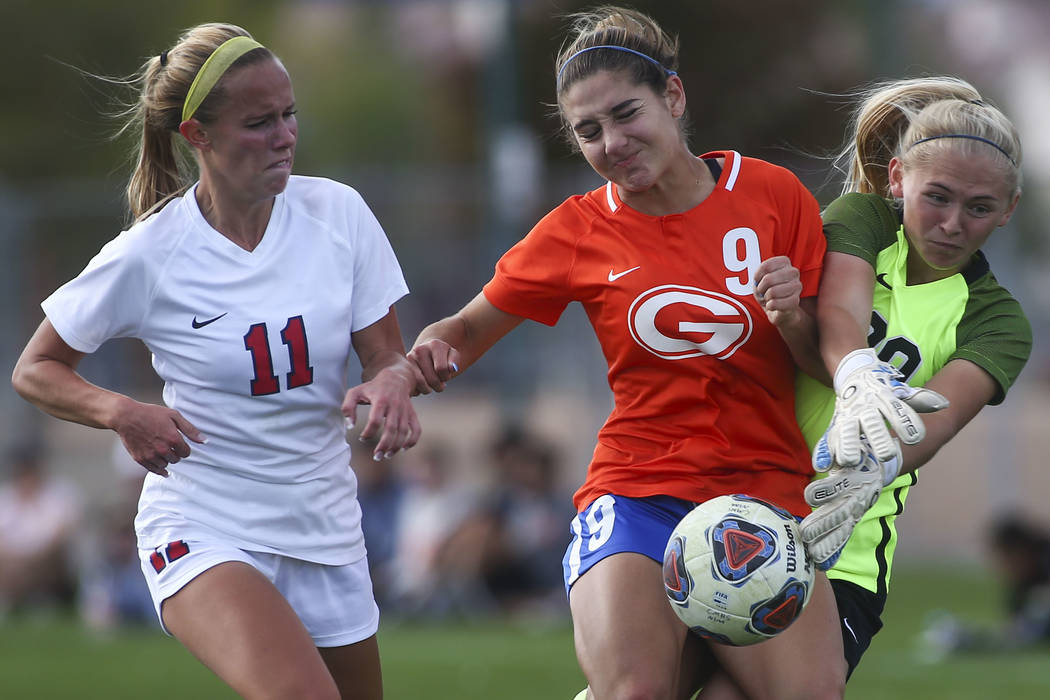 Bishop Gorman's Jaden Terrana (9) fights to maintain control of the ball against Coronado's Taylor Book (00) and Heather Mitchell (11) during the Desert Region girls soccer championship game at Be ...