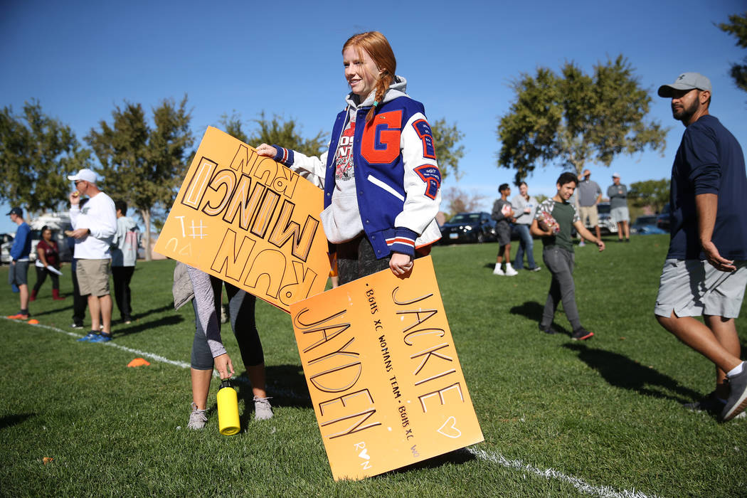 Bishop Gorman junior Sara Gillett, 16, carries signs in support of runners competing in the NIAA 4A Girls Cross Country State Championship at the Veteran's Memorial Park in Boulder City, Saturday, ...