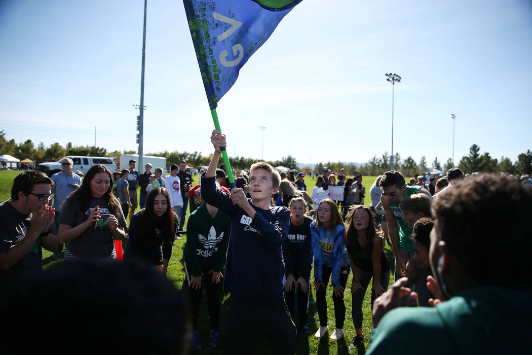 Green Valley freshman Jeffrey Welsh, 15, waves a Green Valley flag during a chant before the NIAA 4A Girls Cross Country State Championship at the Veteran's Memorial Park in Boulder City, Saturday ...