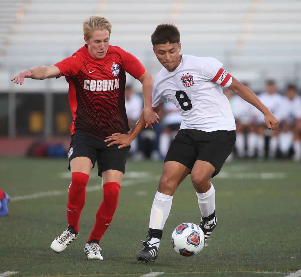 Las Vegas' Daniel Rangel (8) dribbles the ball while under pressure from Coronado's Trenton Tondryk (6) during the Southern Nevada boys soccer championship at Rancho High School in Las Vegas, Mond ...