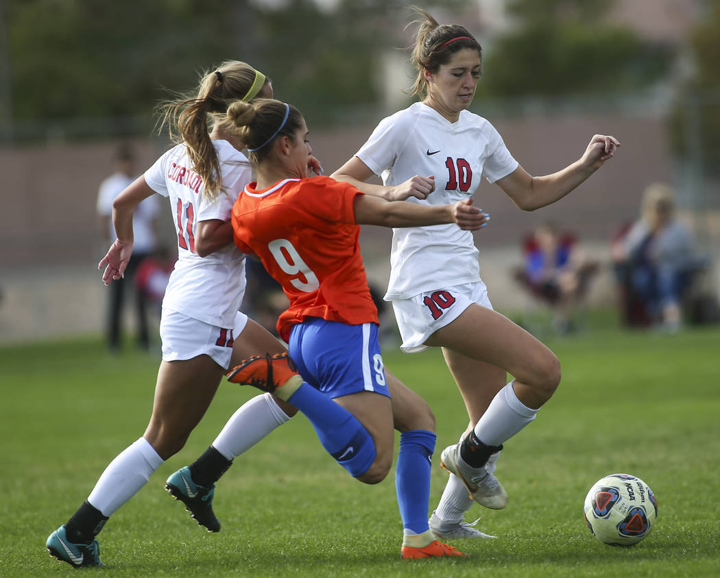 Bishop Gorman's Jaden Terrana (9) tries to get the ball from Coronado's Kaitlyn Kowalchuk (10) and Heather Mitchell (11) during the Desert Region girls soccer championship game at Bettye Wilson So ...