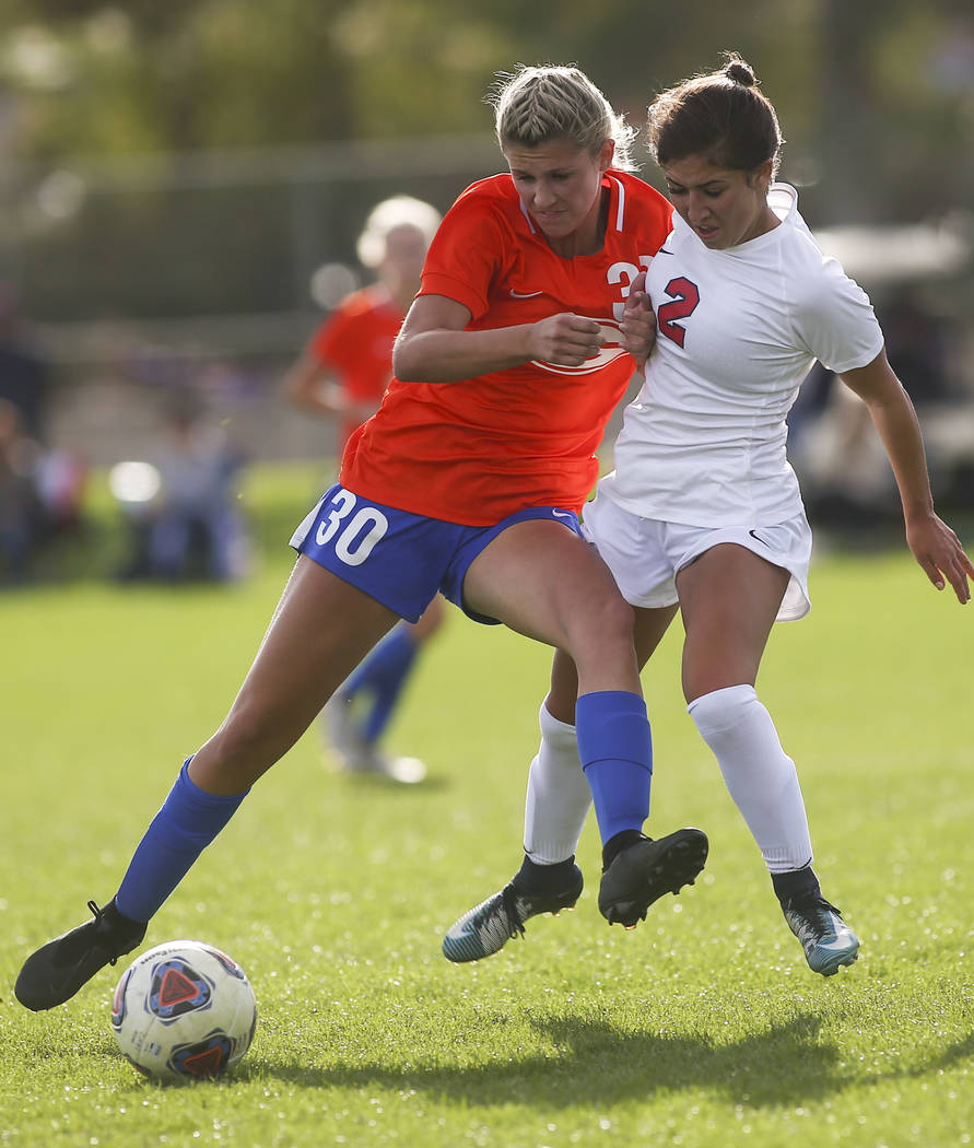 Bishop Gorman's Gianna Gourley (30) battles for the ball against Coronado's Haley Meusy during the Desert Region girls soccer championship game at Bettye Wilson Soccer Complex in Las Vegas on Satu ...
