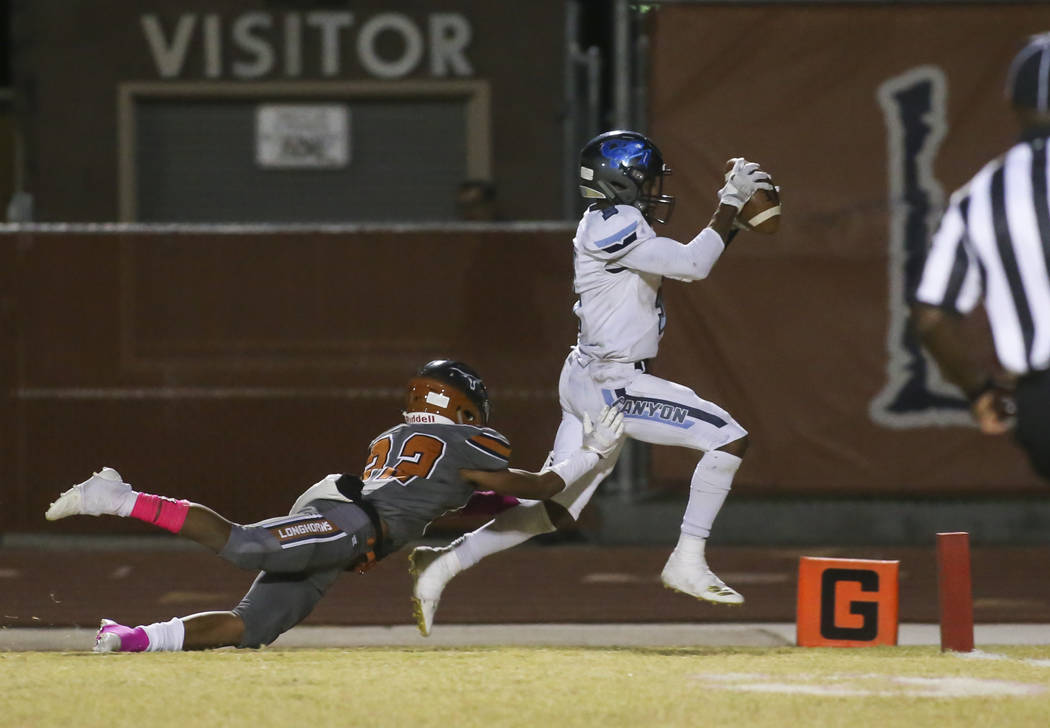 Canyon Springs Jayvion Pugh (3) runs the ball past Legacy's Mason Dailey (22) to score a touchdown during the second half of a football game at Legacy High School in North Las Vegas on Thursday, O ...
