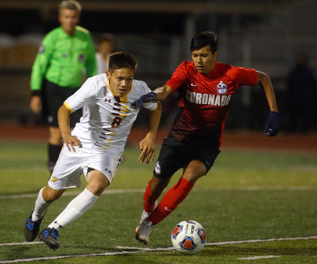 Elderado's Roberto Gonzalez (8) runs with the ball while being covered by Coronado's Moctezuma Maldonado (5) during the state quarterfinal game at Faith Lutheran High School in Las Vegas, Thursday ...