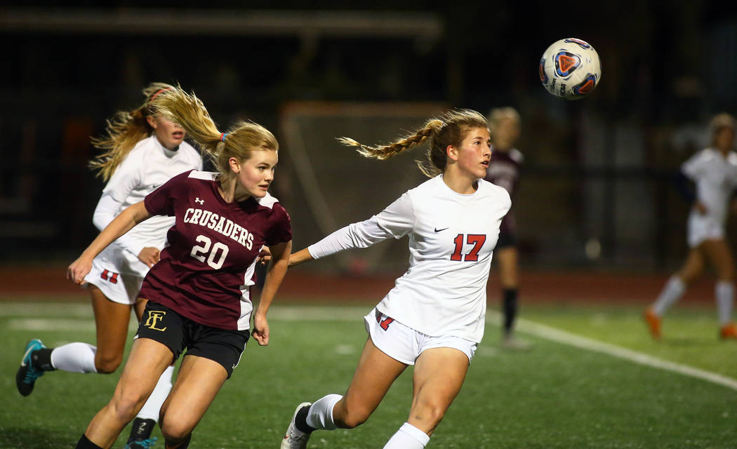 Corando's Emily Wickens (17) runs towards the ball while being covered by Faith Lutheran's McManns (20) during the state quarterfinal game at Faith Lutheran High School in Las Vegas, Thursday, Nov ...