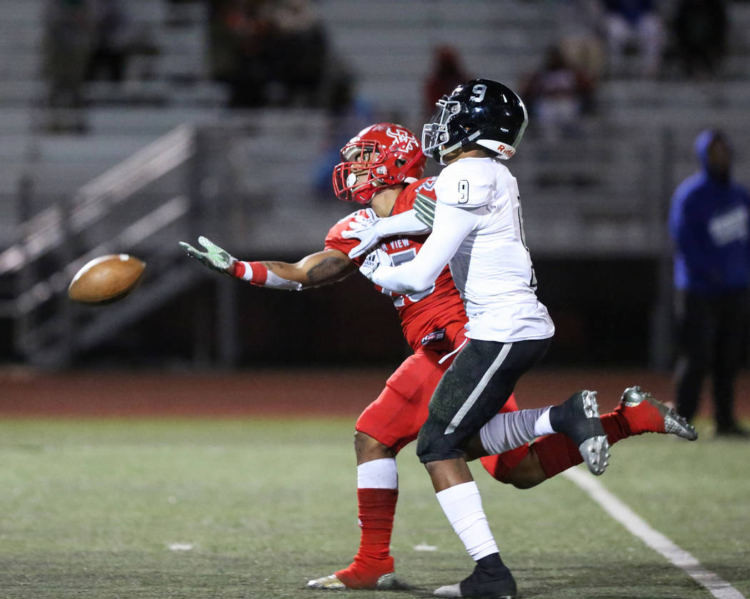 Desert Pines' Corey Clark (9) blocks Arbor View's Kyle Graham (25) from catching the ball during the Mountain Region football semifinal game at Arbor View High School in Las Vegas, Friday, Nov. 9, ...