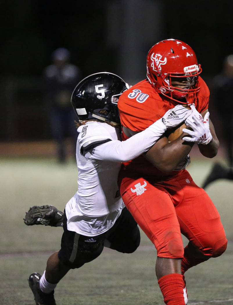 Arbor View's Darius Williams (30) protects the ball while being tackled by Desert Pines' Darius Stewart (5) during the first half of the Mountain Region football semifinal game at Arbor View High ...