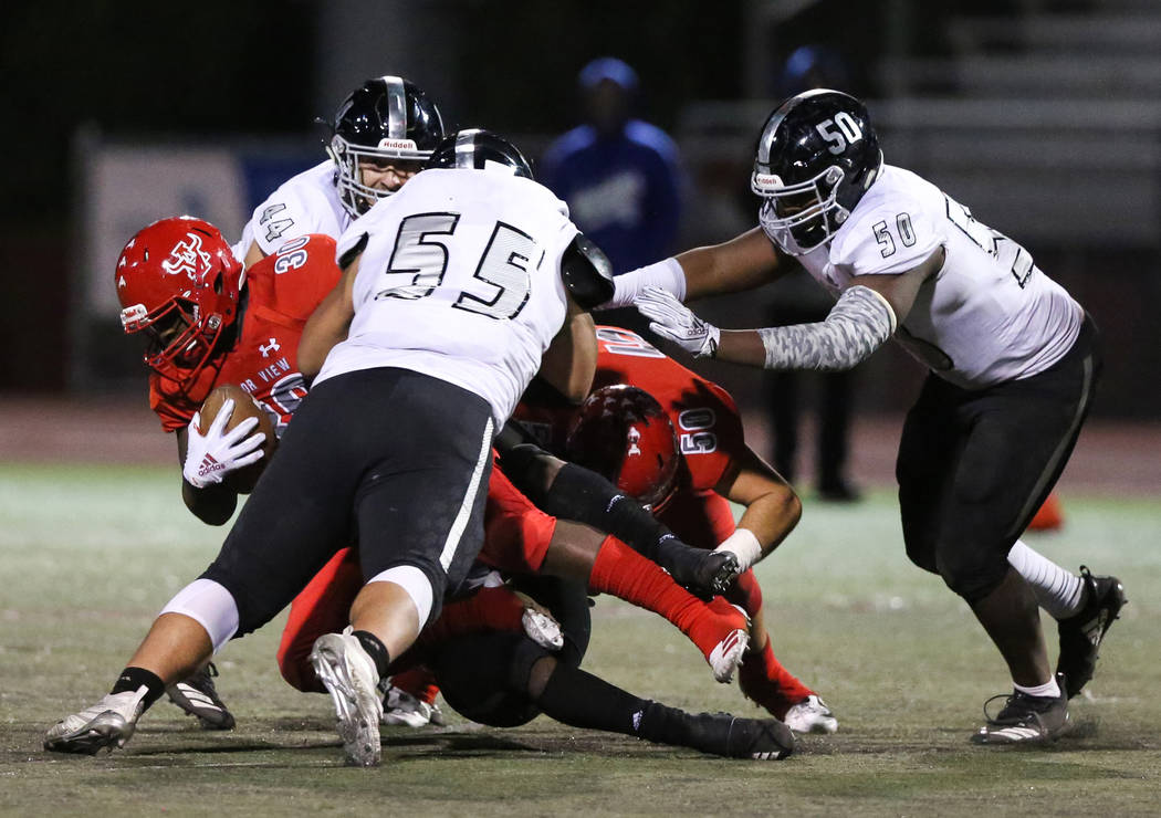 Arbor View's Darius Williams (30) gets tackled while in possession of the ball during the first period of the Mountain Region football semifinal game at Arbor View High School in Las Vegas, Friday ...