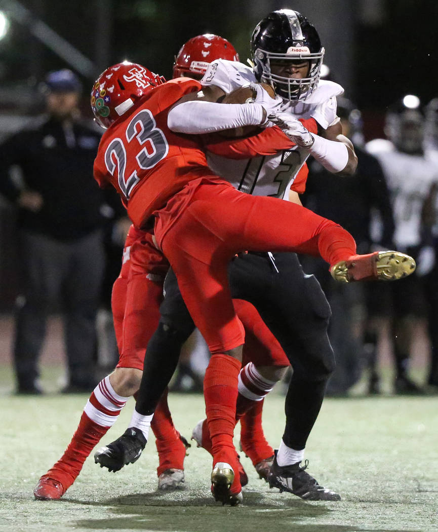 Desert Pines' Darnell Washington (13) protects the ball while being tackled by Arbor View's Darius Harrison (23) during the first half of the Mountain Region football semifinal game at Arbor View ...
