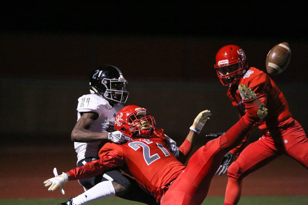 Desert Pines' Ezekiel Washington (21) holds back Arbor View's Niles Scafati-Boyce (27) during second half of the Mountain Region football semifinal game at Arbor View High School in Las Vegas, Fri ...