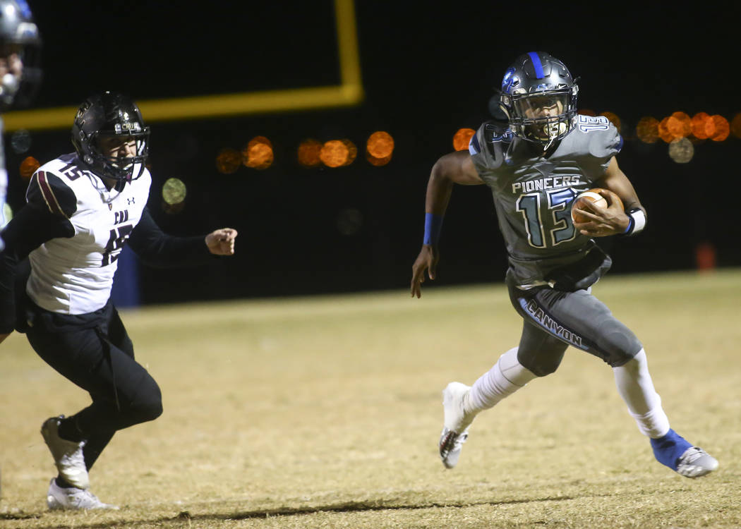 Canyon Springs' Xavier DeLong (13) runs the ball past Faith Lutheran's Connor Bourne (15) on the way to score a touchdown during a Mountain Region football semifinal game at Canyon Springs High Sc ...